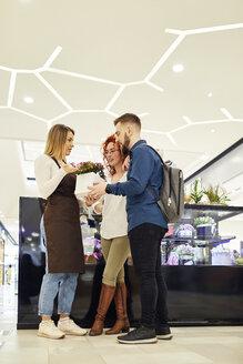 Shop assistant advising couple in flower shop - ZEDF01971
