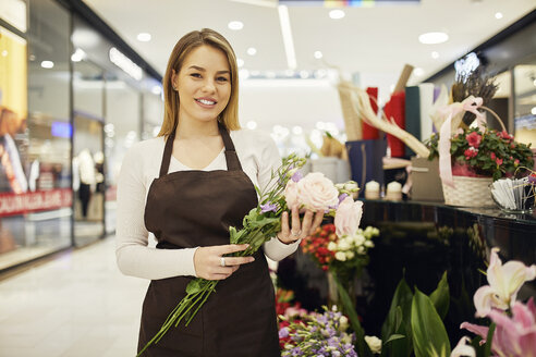 Portrait of smiling florist holding flowers in flower shop - ZEDF01977