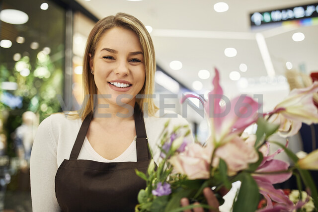 Portrait of smiling florist holding flowers in flower shop - ZEDF01980