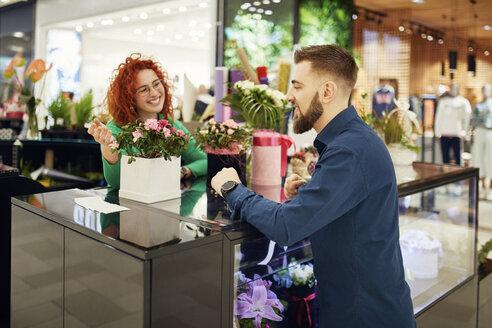 Florist talking to customer in flower shop - ZEDF01983