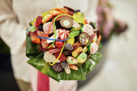 Close-up of woman holding candy bouquet - ZEDF01992