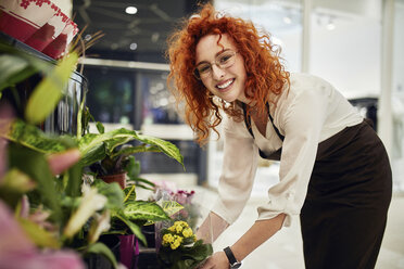 Portrait of smiling florist arranging flowers in flower shop - ZEDF01995