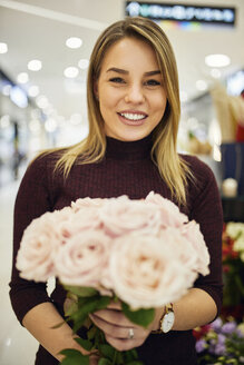 Portrait of smiling woman holding bunch of flowers in flower shop - ZEDF01998