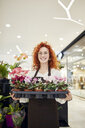 Portrait of smiling florist holding tray of potted plants in flower shop - ZEDF02001