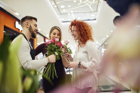 Florist advising customers in flower shop - ZEDF02010