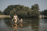 Netherlands, Schiermonnikoog, pregnant mother with daughter in a lake - DWF00332