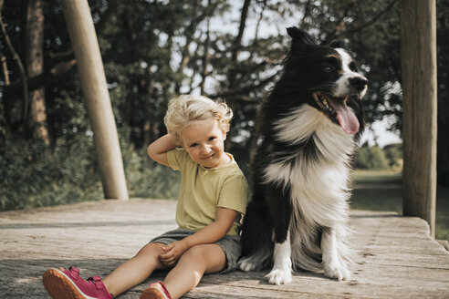 Netherlands, Schiermonnikoog, girl with Border Collie sitting on boardwalk in the forest - DWF00335