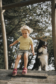 Netherlands, Schiermonnikoog, girl with Border Collie on boardwalk in the forest - DWF00338