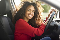 Portrait of happy young woman in a car - JSMF00803