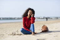 Thoughtful young woman sitting on the beach - JSMF00812