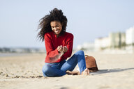 Happy young woman sitting on the beach - JSMF00815