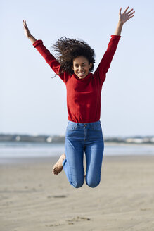 Carefree young woman jumping on the beach - JSMF00821