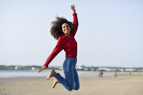 Spain, Andalusia, Puerto de Santa María. Happy young black woman with curly hair feeling the freedom jumping with open arms on the beach. Lifestyle and travel concepts. - JSMF00824