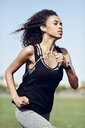 Sporty young woman with earphones running - JSMF00839