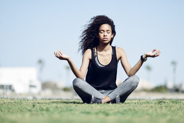 Sporty young woman doing yoga on lawn - JSMF00845