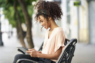 Smiling young woman sitting on a bench using tablet - JSMF00851