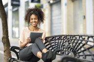 Portrait of happy young woman sitting on a bench using tablet - JSMF00854