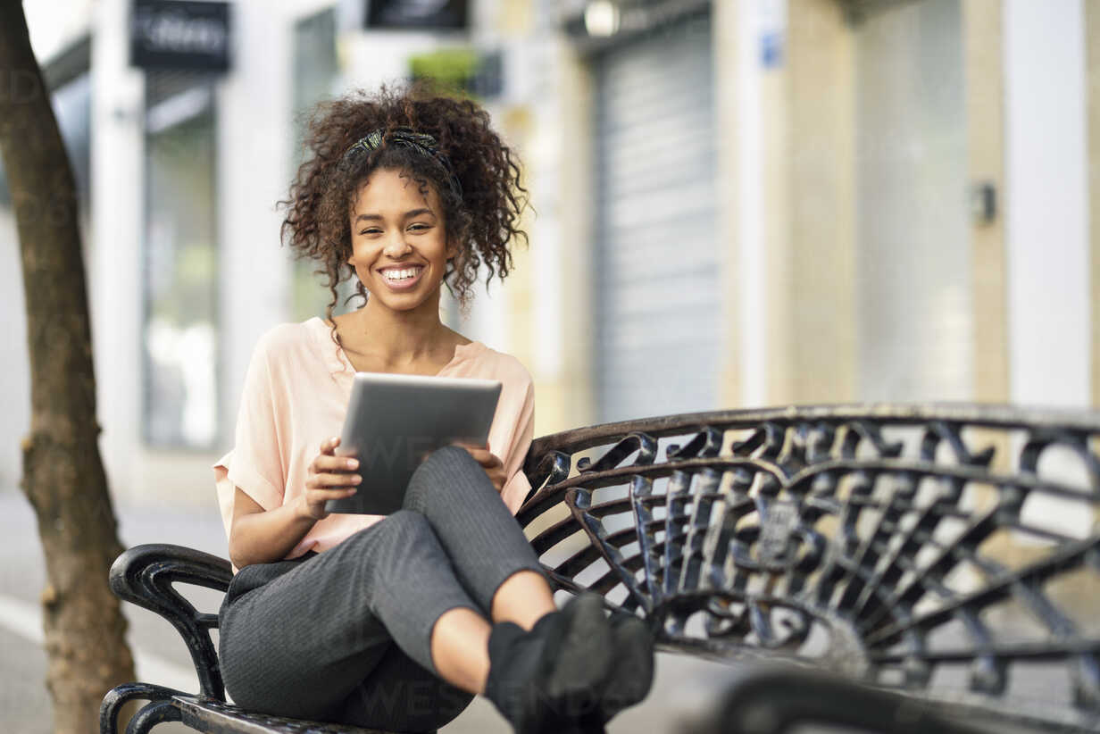 Portrait of happy young woman sitting on a bench using tablet - JSMF00854 - Javier Sánchez Mingorance/Westend61