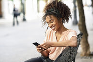 Smiling young woman sitting on a bench using cell phone - JSMF00860
