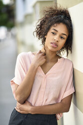Serious young woman leaning against a wall looking around - JSMF00869