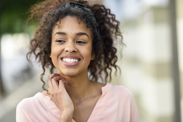 Portrait of smiling young woman in the city - JSMF00872