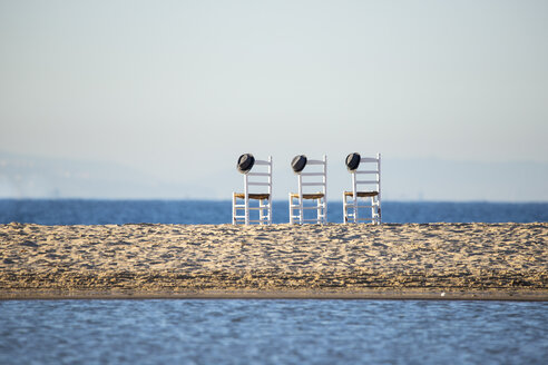 Three empty chairs with hats side by side in front of the sea - KBF00592