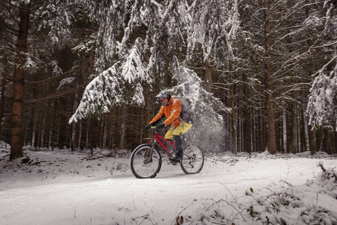Man riding mountainbike on path in winter forest - SEBF00044