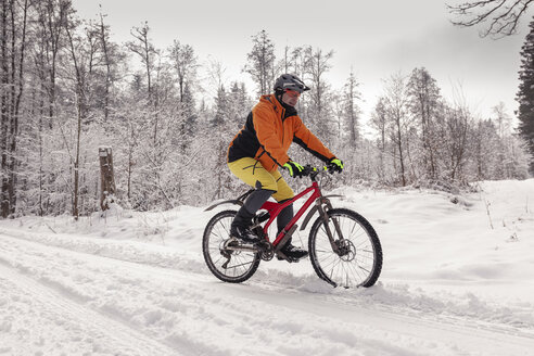 Man riding mountainbike on path in winter forest - SEBF00053