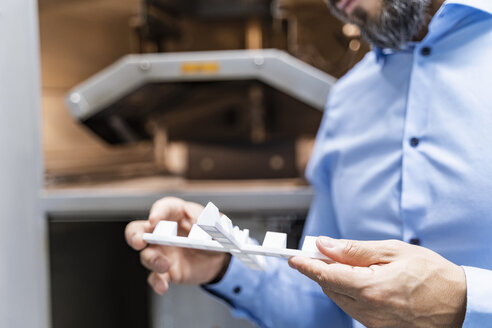 Close-up of man holding workpiece at 3d printer - DIGF06199