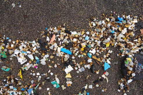 Spain, Canary Islands, Lanzarote, Playa Famara, microplastics, washed up on dark lava sand - SIEF08422