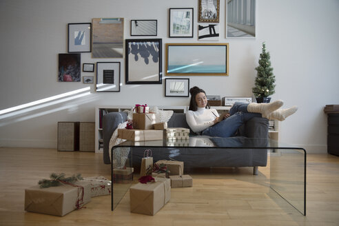 Cozy young woman wrapping Christmas gifts in living room - HEROF28495