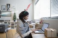 Young woman in Christmas reindeer antlers using laptop - HEROF28501