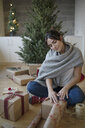 Young woman wrapping Christmas gifts on floor - HEROF28519