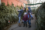 Happy family taking selfie, shopping for Christmas tree at Christmas market - HEROF28543