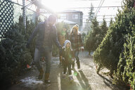 Family shopping for Christmas tree at Christmas market - HEROF28570