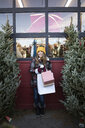 Portrait happy woman with shopping bags standing between Christmas trees at Christmas market - HEROF28576