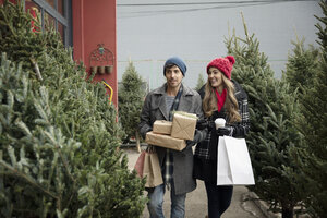 Couple shopping for gifts and Christmas tree at Christmas market - HEROF28609