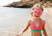 Cute girl in swimming goggles on beach, Portoferraio, Tuscany, Italy - CUF49769