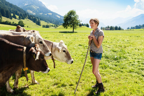 Woman bonding with herd of cows on field, Sonthofen, Bayern, Germany - CUF49862