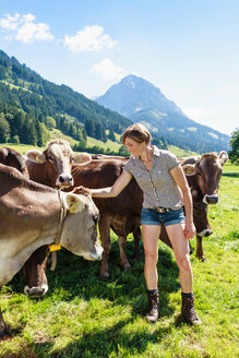 Woman bonding with herd of cows on field, Sonthofen, Bayern, Germany - CUF49865