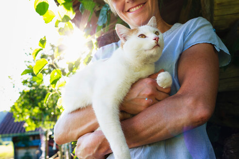 Woman carrying cat in countryside - CUF49889