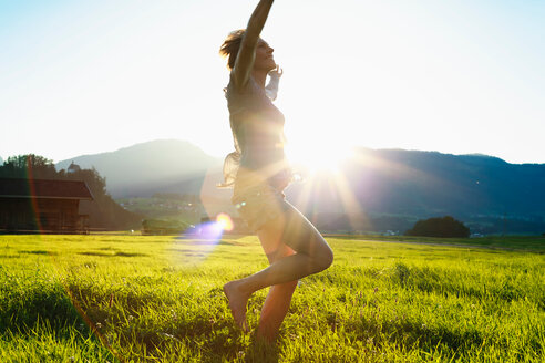 Woman dancing on grass in countryside, Sonthofen, Bayern, Germany - CUF49904