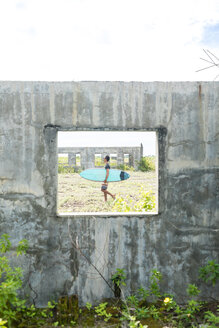 Surfer seen through window of abandoned building, Abulug, Cagayan, Philippines - CUF49931