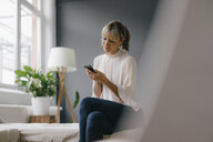 Woman sitting on couch, using smartphone - JOSF03139