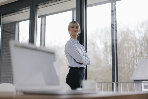 Successful businesswoman in conference room, smiling, with arms crossed - JOSF03154