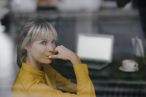 Blond businesswoman sitting at window, thinking - JOSF03199