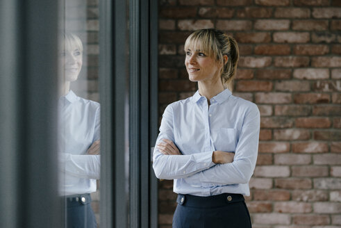 Confident businesswoman looking out of window, with arms crossed - JOSF03208