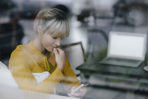 Blond businesswoman sitting at window, doing a paymant with smartphone and creditcard - JOSF03220
