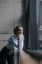 Confident businesswoman standing at window, thinking - JOSF03250