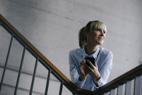 Businesswoman leaning on railing, using smartphone - JOSF03253